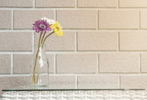 Bunte blume der nahaufnahme auf backsteinmauerbeschaffenheitshintergrund