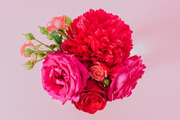 Bunte blumen-, pfingstrosen- und rosenzusammensetzung der flachen lage auf rosa, sauberem kopienraum
