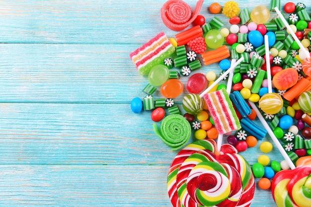 Bunte bonbons auf hölzernem hintergrund