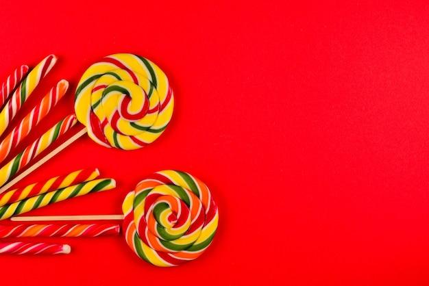 Bunte bonbons auf rotem grund. lutscher. ansicht von oben. platz kopieren.