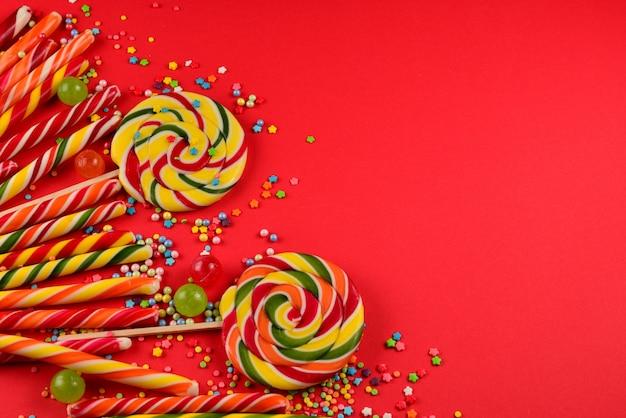 Bunte bonbons auf rotem grund. lutscher. draufsicht. speicherplatz kopieren.