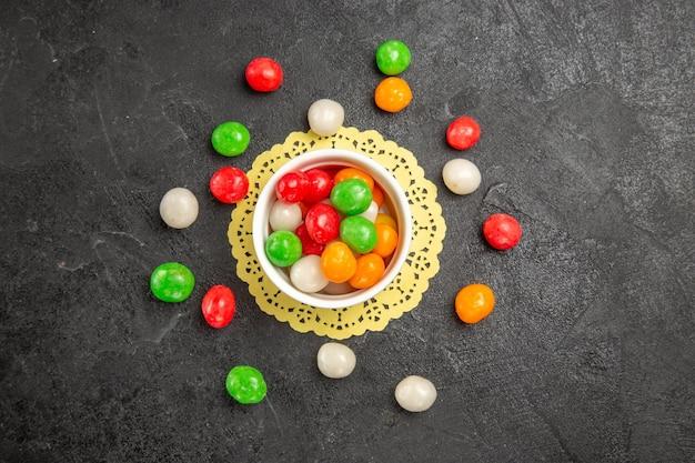 Bunte bonbons der draufsicht auf dunklem hintergrundfarbe regenbogen süßer tee