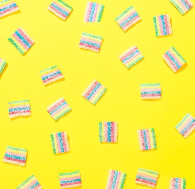 Bunte bonbons der draufsicht auf gelbem hintergrund
