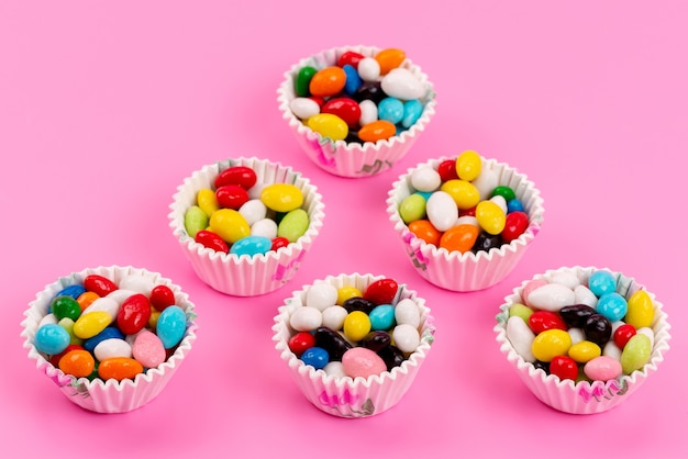 Bunte bonbons der draufsicht innerhalb der papierverpackungen auf rosa