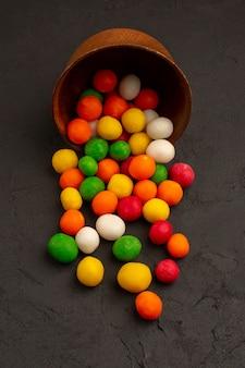 Bunte bonbons der draufsicht innerhalb des braunen topfes auf dem dunklen boden