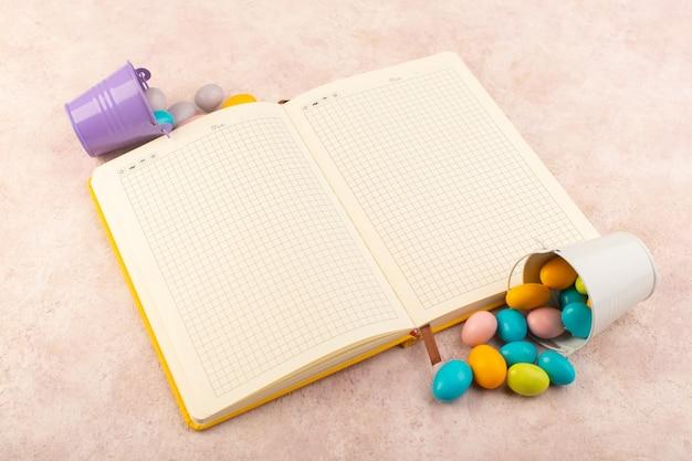 Bunte bonbons der draufsicht mit dem heft auf der süßen süßigkeitsfarbe des rosa schreibtischzuckers