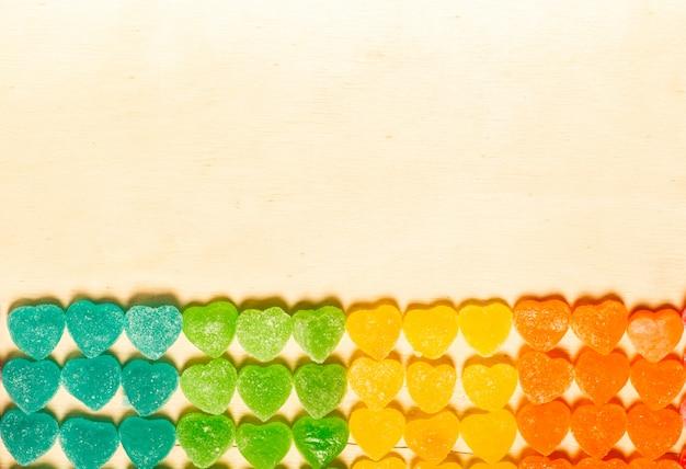 Bunte bonbons der süßigkeit und des gelees herz-förmig auf hölzernem hintergrund