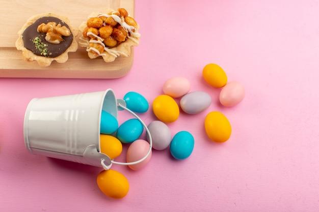 Bunte bonbons der vorderansicht mit kleinen schokoladenkuchen auf der süßen farbe des rosa schreibtischzuckers