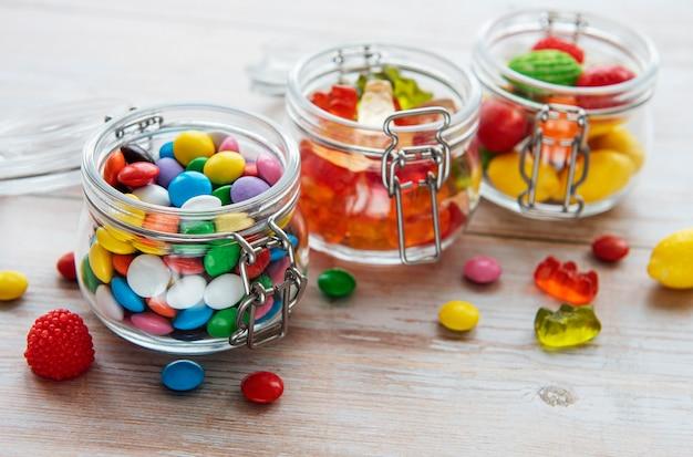 Bunte bonbons, gelee und marmelade in gläsern auf dem tisch