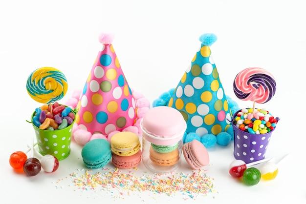 Bunte bonbons und lutscher der französischen macarons der vorderansicht zusammen mit lustigen geburtstagskappen auf weißer, feierlicher farbe der feierfarbe