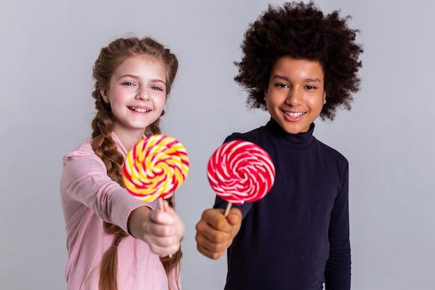 Bunte bonbons. ziemlich gut aussehende kinder, die in der nähe bleiben und für ein fotoshooting posieren, während sie rollkragenpullover tragen