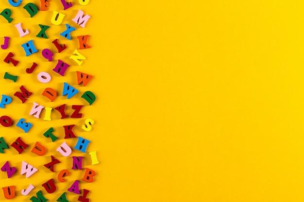 Bunte buchstaben des englischen alphabets auf gelbem grund