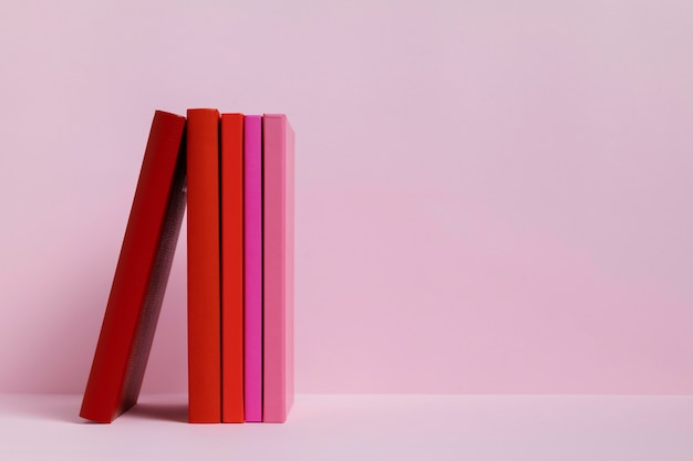Bunte bücher mit rosa hintergrund