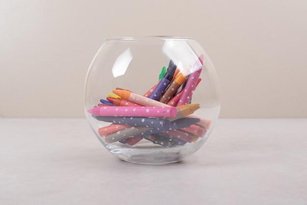 Bunte buntstifte im glas auf weißem hintergrund