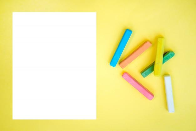 Bunte buntstifte und ein blatt weißes papier auf einem gelben
