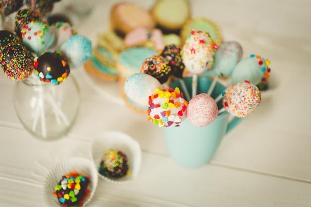 Bunte cake pops in tassen auf weißem holzschreibtisch