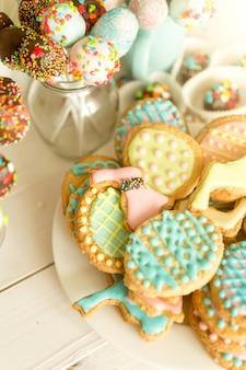 Bunte cake pops und kekse auf weißem holzschreibtisch