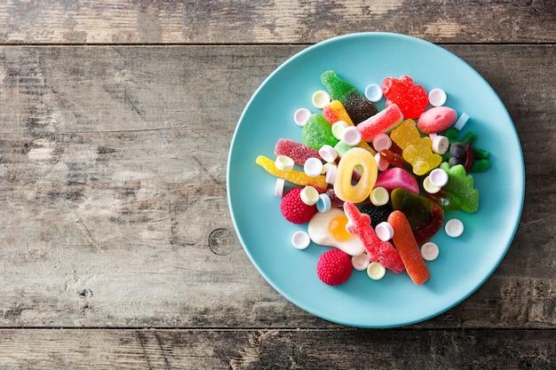 Bunte childs bonbons und festlichkeiten in der platte auf holztisch