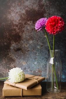 Bunte chrysanthemenblumen in glasvase mit eingewickelten geschenkboxen