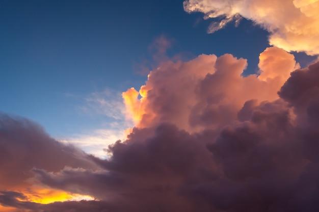 Bunte cumulonimbus-wolken beleuchtet von sonnenuntergangslicht im kontrast zum blauen himmel