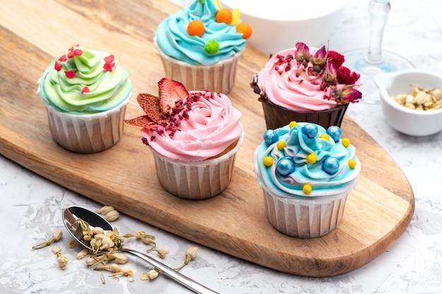Bunte cupcakes mit unterschiedlicher moderner dekoration auf holzbrett mit löffel und zutaten auf blauem hintergrund