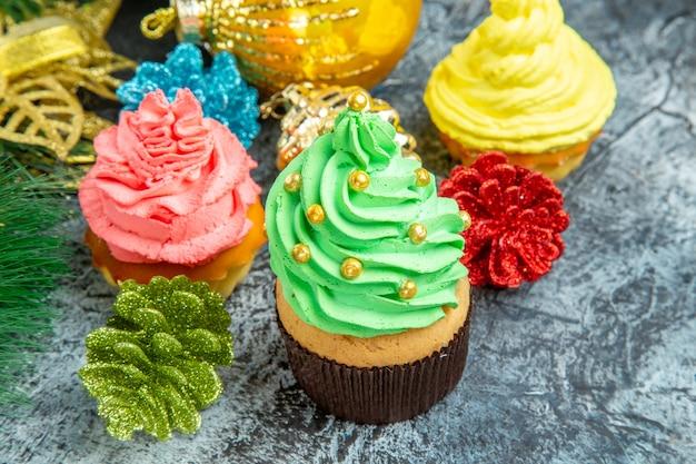 Bunte cupcakes-weihnachtsverzierungen der vorderansicht auf grauem foto des neuen jahres