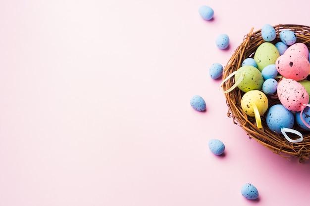 Bunte dekor ostereier in einem nest auf rosa