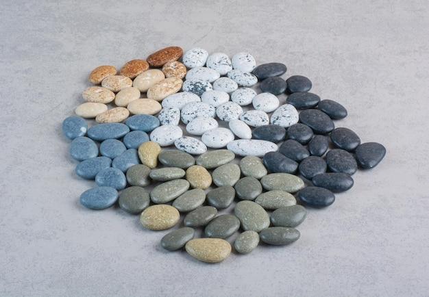 Bunte dekorative steine zum basteln auf betonoberfläche.