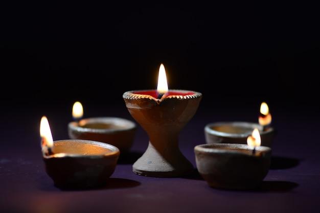 Bunte diya-lampen (laterne) aus ton, die während der diwali-feier beleuchtet wurden. grußkarten-design indisches hindu-licht-festival namens diwali.