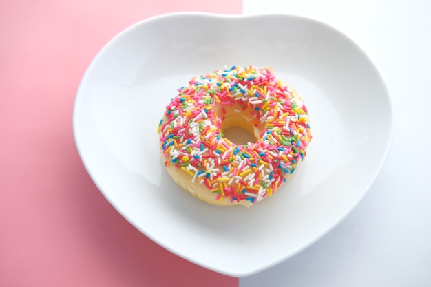 Bunte donuts auf herzförmigem teller