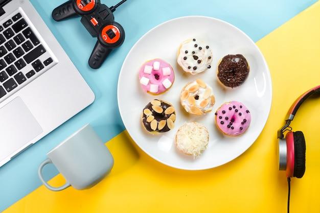 Bunte donuts kombiniert mit laptops und gegenständen im büro
