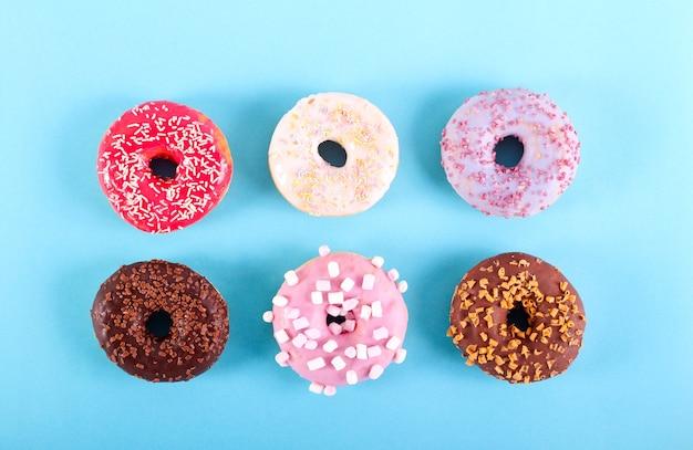 Bunte donuts über blauem hintergrund, draufsicht