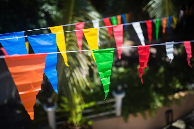 Bunte dreieckflaggen, die an den seilen im freien hängen. hoher hoher pfosten mit dem bunten dreieckflaggenhängen