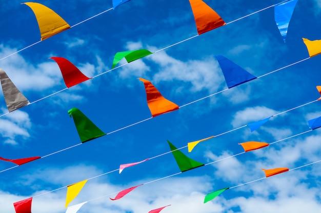 Bunte dreieckige markierungsfahnenzeile, die durch wind auf weißwolke des blauen himmels sich bewegt