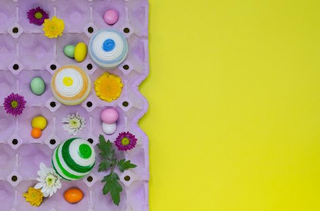 Bunte eier verzieren mit strickender wolle für ostertag und festival, die in purpurrote eierablage gesetzt werden.