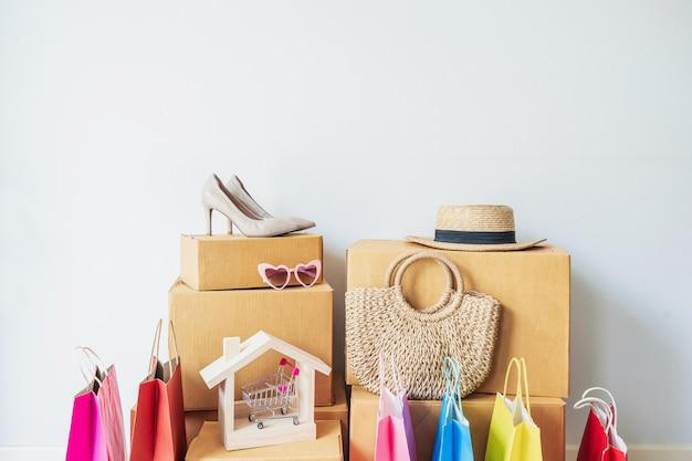 Bunte einkaufstasche mit stapel von pappkartons und modeartikeln zu hause