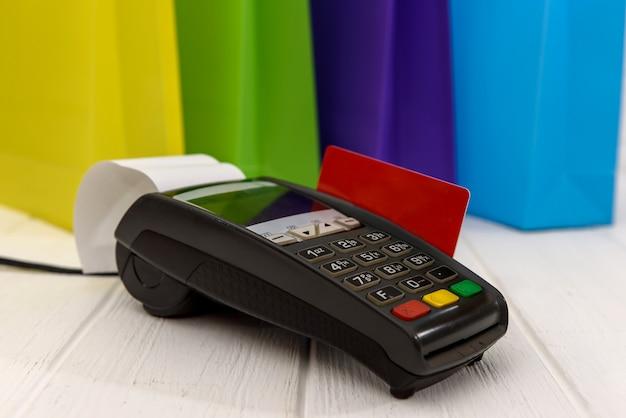Bunte einkaufstaschen mit terminal und kreditkarte