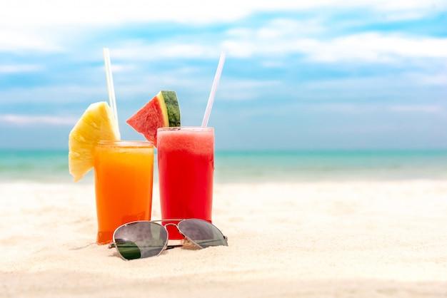 Bunte erfrischende tropische fruchtsaftgetränke am sommerstrand