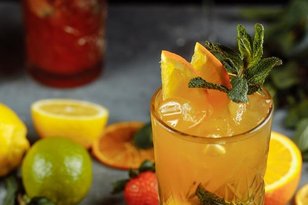 Bunte erfrischungsgetränke für den sommer, kalter erdbeerlimonadensaft mit eiswürfeln in den gläsern garniert mit geschnittenen frischen zitronen.