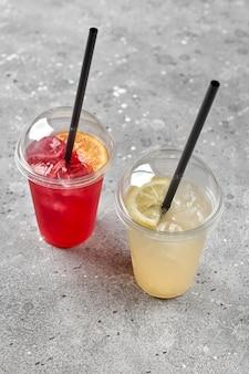 Bunte erfrischungsgetränke limonade in plastikgläsern, außenstand mit essen zum mitnehmen, rote limonade mit eis in einem plastikglas zum mitnehmen