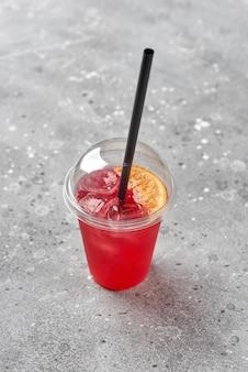 Bunte erfrischungsgetränklimonade in plastikgläsern, außenstand mit essen zum mitnehmen, rote limonade mit eis in einem plastikglas zum mitnehmen