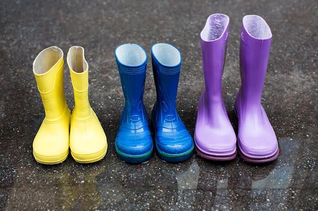 Bunte familienstiefel am regnerischen tag auf der straße