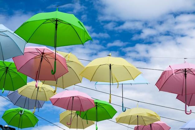 Bunte fantastische regenschirmlinie verzieren das bewegen im freien durch wind auf weißwolke des blauen himmels