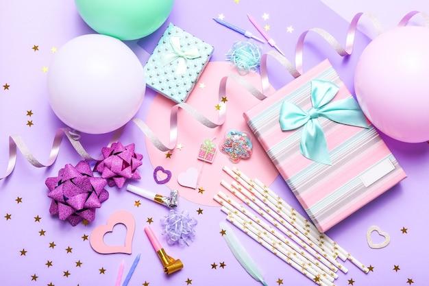 Bunte feier mit verschiedenen partykonfetti, luftballons, geschenken und dekoration auf flieder