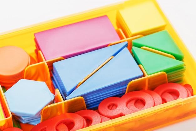 Bunte figuren und zahlen für kinder in einer box. ein werkzeug zur entwicklung des kindlichen denkens.