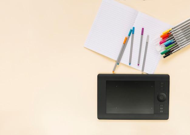 Bunte filzstifte auf notizbuch mit grafischer digitaler tablette über farbigem hintergrund