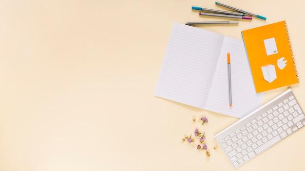 Bunte filzstifte; blume; notizbuch mit tastatur über farbigem hintergrund