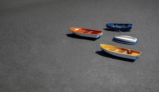 Bunte fischerboote, am schwarzen sandstrand von los molinos auf der insel fuerteventura, spanien