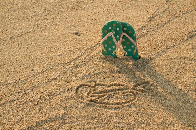 Bunte flip-flops und herzform auf weißem sandstrand im weinlesestil