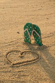Bunte flip-flops und herzform auf weißem sandstrand